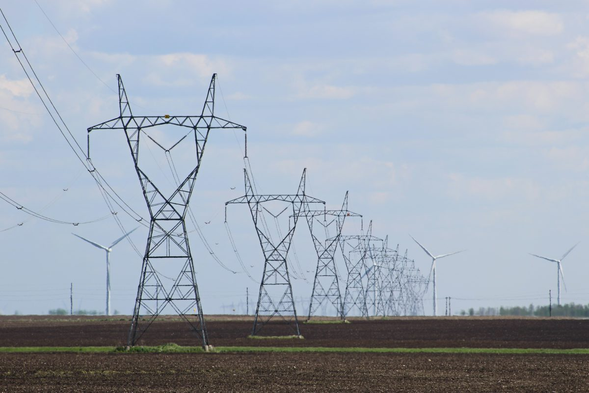 Lined up transmission towers in an open fields